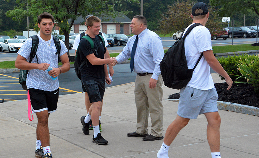 The high school principal greets students as they walk into school